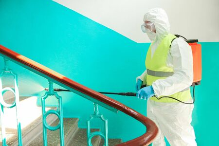 A specialist in a protective suit disinfects the railing against coronavirus infection. Epidemic control.