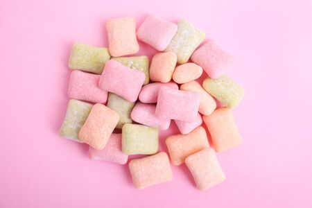 Pillows of multi-colored chewing gum on a pink background.