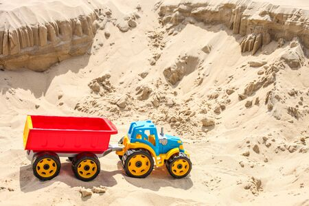 Children's toy tractor on the sea sand. Beach holiday