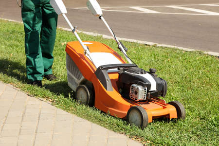 A worker is cutting the grass with a lawn mower in a city park.