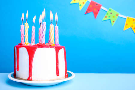 White cream cake with red icing and a candle on a blue background. Birthday concept.