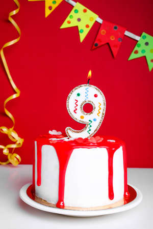 White cream cake with red icing and a candle on a red background. Birthday concept.