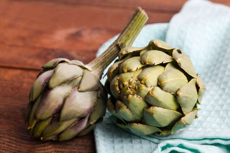 Fresh artichokes on blue kitchen towel on a brown background. 写真素材