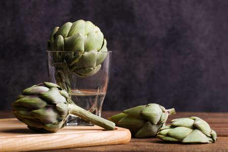 Fresh artichokes in a glass of water.