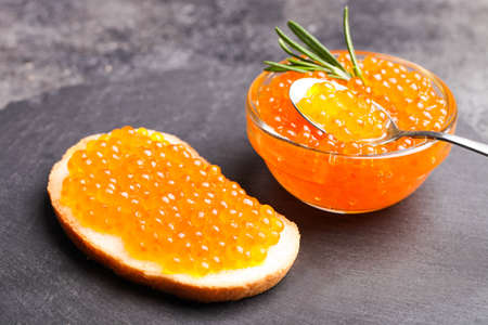 Sandwich with red chum salmon caviar and rosemary on a black background.