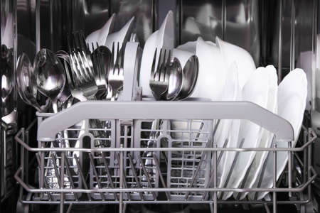 Open built-in dishwasher with clean dishes. Stock Photo