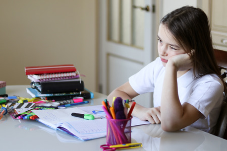 Young schoolgirl is upset and tired of doing school homework at home