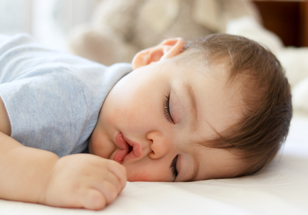 Cute little baby sleeping on stomach with funny open mouth. Daytime sleeping. Close-up. Stock Photo