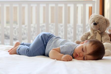 Śmieszne dziecko śpi na brzuchu na łóżku w domu. Pozycja spania do spania w ciągu dnia dziecka