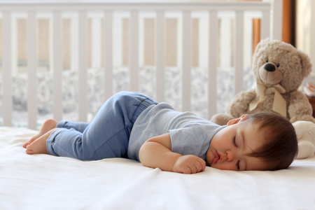 Funny baby sleeping on his stomach on bed at home. Child daytime bottom up sleeping position Reklamní fotografie - 96131177