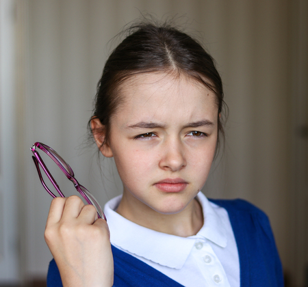 Beautiful schoolgirl in school uniform screwing up her eyes trying to see something holding glasses in her hand Stock Photo