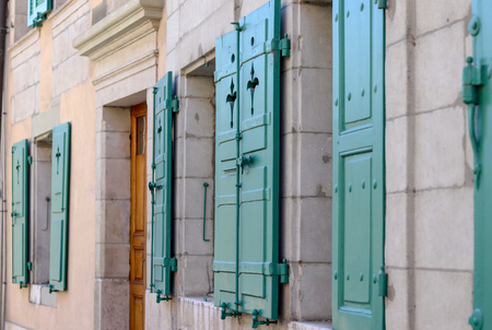 Facade of old house with windows with open green shutters and wooden door in old Nyon town, Switzerland Stock Photo