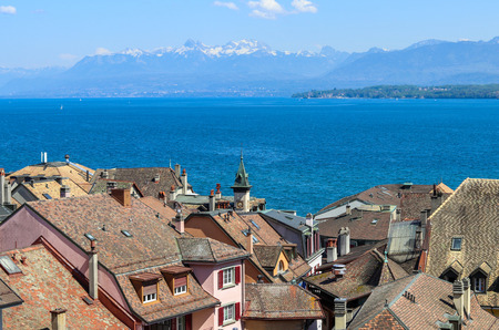 Beautiful view at Geneva lake and french Alps mountains with snow tops through roofs of old town of Nyon, Switzerland Stock Photo