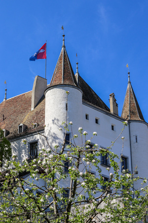 View at Nyon castle with flag waving on the roof through blooming tree, Switzerland Editorial