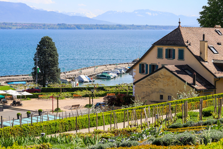 Beautiful view at lake Geneva or Lac Leman and Alp mountains through the garden on hill of Nyon, Switzerland