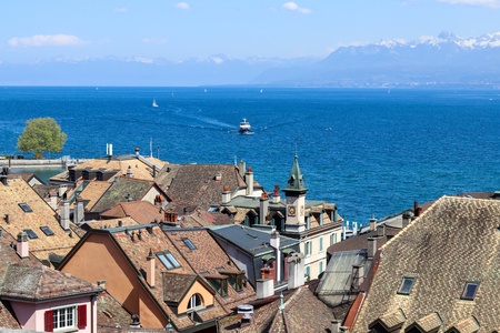 Amazing view over the roofs of old Nyon town at blue Geneva lake or Lac Leman with sailboats and ship and mountains with snow tops at background, Switzerland, Europe Editorial