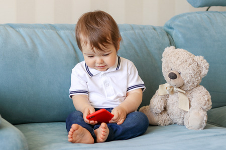 Cute smiling baby boy playing on smartphone sitting on sofa with teddy bear at home, parenting control concept, new generation Stock Photo