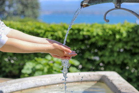 Close-up photo of young girl washing hands in city fountain with water splashing on them with a lot of drops, outdoors at sunny day, green hedge and lake on background Stock Photo