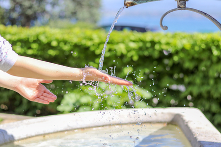 Closeup photo of young girl washing hands in city fountain with water splashing on them with a lot of drops, outdoors at sunny day, green hedge and lake on background