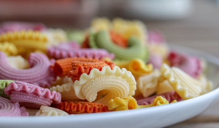 Colorful green, yellow, white, orange and pink italian crown pasta on white plate staying on wooden table, close-up. Multicolor pasta texture.  Front focus Stock Photo