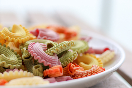 Colorful green, yellow, white, orange and pink italian crown pasta on white plate staying on wooden table, close-up. Multicolor pasta texture.  Front focus, copy space