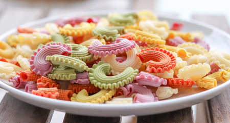 Colorful green, yellow, white, orange and pink italian crown pasta on white plate, close-up. Multicolor pasta texture pattern.  Long wide banner
