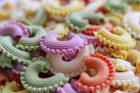 Background of colorful green, yellow, white, orange and pink italian crown pasta as creative food texture, close-up. Multicolor pasta texture pattern.  Front focus