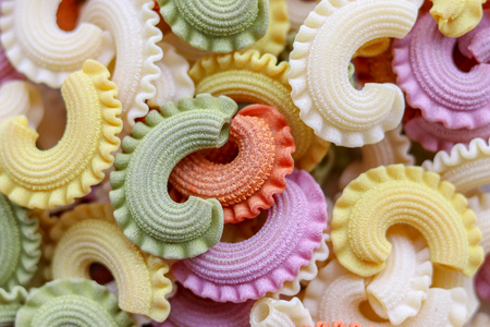 Background of colorful green, yellow, white, orange and pink italian crown pasta as creative food texture, close-up, top view. Multicolor pasta texture pattern background.