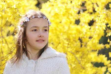 Portret of smiling pretty little girl with handmade hair wreath on yellow Forsythia blossom background