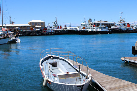 Boat moored at the pier in blue marine with big vessels and seagulls on background, port in V&A Waterfront, Cape Town