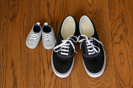 Father and son sneakers staying next on the wooden floor, top view. Fathers day Stock Photo
