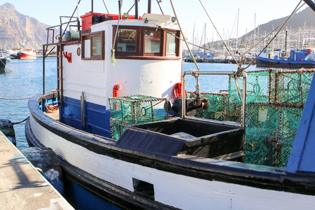 Fishing boat with lobster traps moored in the port in Hout Bay harbor, Cape Town, South Africa
