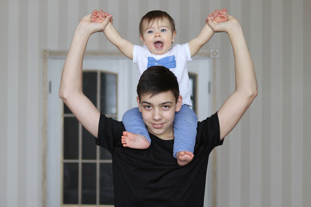 Smiling teenager boy holding his little brother sitting on his neck Stock Photo