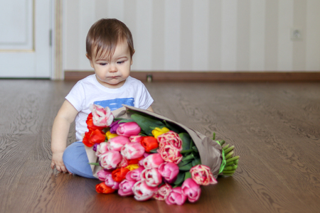 Cute little thoughtful baby boy sitting near the bunch of tulips, thinking and looking down Stock Photo