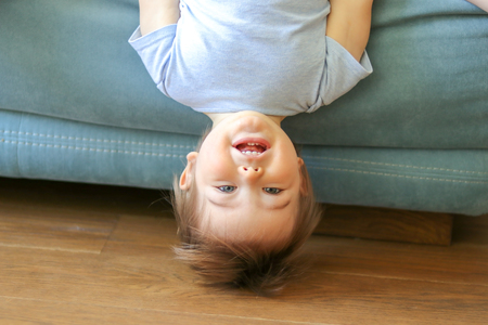 Cute funny little baby boy hanging upside down on sofa looking at camera, smiling with his first teeth playful child having fun at home on couch, standing on head, head-shot portrait of happy grey-eyed kid with light hair playing at home