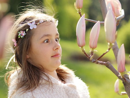 Cute fun little girl with handmade hair wreath surprised and amazed looking at magnolia buds in spring garden, close-up, funny emotion