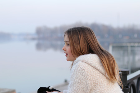 Beautiful little girl in white coat looking at the river, surprised