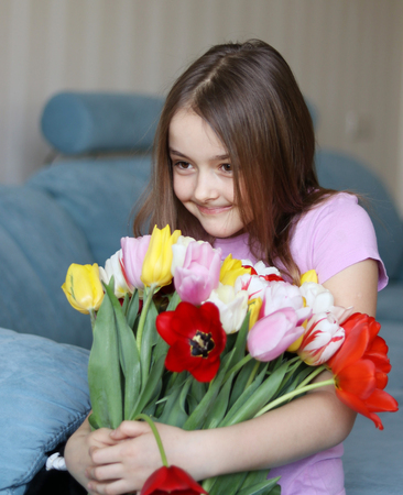 Pretty little shy girl holding big bouquet of tulips