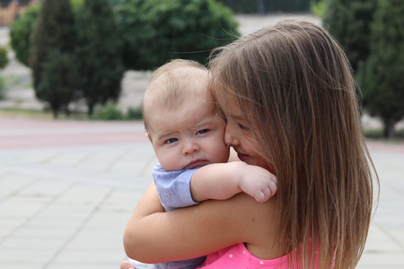 Young girl holding her newborn brother in her arms and looking at him with tenderness, outdoors