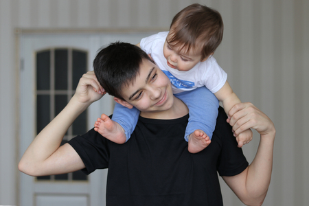 Happy smiling teenager boy holding his little brother sitting on his neck. Family concept Stock Photo