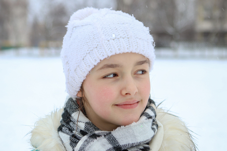Winter portrait of beautiful smiling little girl in white hat looking to the side with droplets on her eyelashes Stock Photo