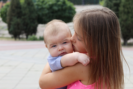 Beautiful young girl holding her newborn brother and kissing him tenderly, outdoors