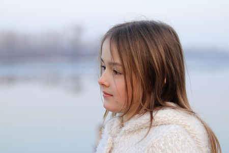 Portrait of beautiful little girl in white coat looking thoughtfully on the left, outdoors Stock Photo