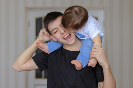 Teenager boy holding his little brother sitting on his neck and playing with him. Family concept, siblings