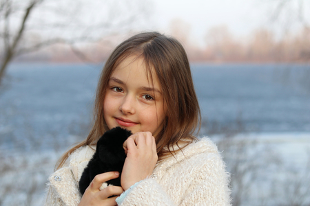 Beautiful little brown-eyed girl looking at camera hugging her soft toy, close-up, outdoors