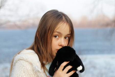 Beautiful little brown-eyed girl looking at camera holding her soft toy, close-up, outdoors