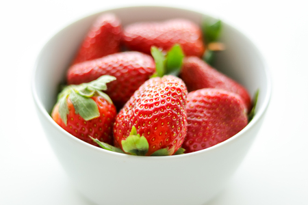 Fresh, bright juicy strawberries in white bowl isolated on white background, close-up