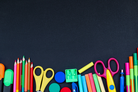 Bright school supplies on blackboard background ready for your design, copyspace above Stock Photo
