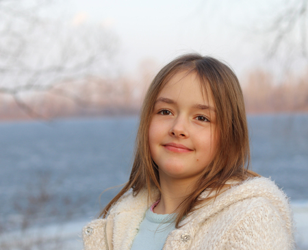 Portrait of beautiful smiling little girl at sunset, water on background Stock Photo