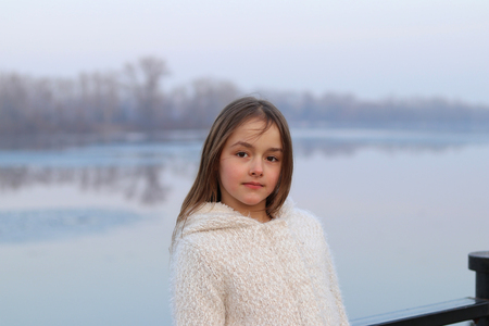 Beautiful little brown-eyed girl in white coat looking at camera seriously, outdoors Stock Photo